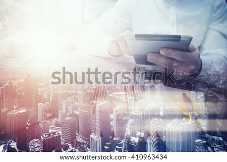Double exposure photo.Man touching modern tablet.Investment trader manager working new private banking project office.Using electronic device.City skyscrapers background,film and bokeh effect.