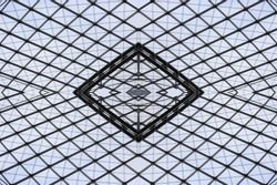 Double exposure photo of structural glass roof / ceiling / dome provided this fictional hi-tech architecture fragment with grid structure / pattern.