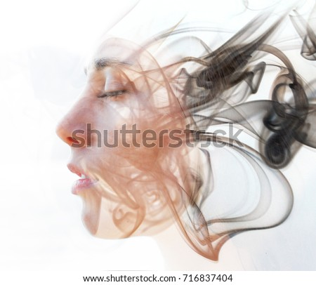Double exposure portrait of a young fair-skinned woman and a smoky texture dissolving into her facial features