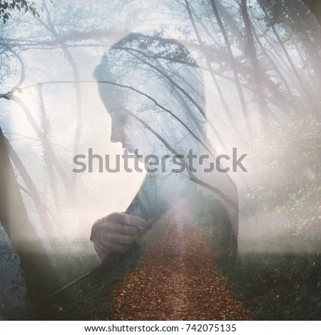 Double exposure portrait of a young thoughtful woman combined with photograph of a foggy forest road in autumn. Conceptual image showing mystery, loneliness, negative emotions