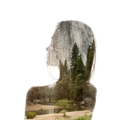 Double exposure portrait of a young thoughtful woman combined with photograph of green forest trees in mountains. Conceptual image showing unity of human with nature. Ecology, freedom, environment