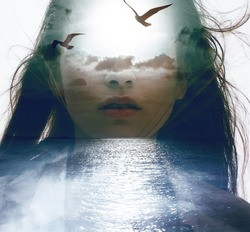 Double exposure portrait of a young woman combined with photograph of nature ocean, clouds and flying birds