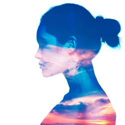 Double exposure portrait of beautiful girl in profile. Young woman and sunset or sunrise sky.