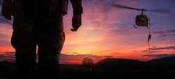 Double exposure silhouette back side view soldier helicopter under army training at sunset mountain twilight sky background.
