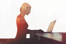 Double exposure silhouette of businesswoman is working in office with net-book while sitting at desktop. Hipster girl internet user of laptop computer is connecting to 5 generation wireless system