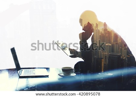 Double exposure silhouette of man skilled managing director is analyzing activities of the company by using touch pad and net-book. Thoughtful economist is reading news in network via digital tablet