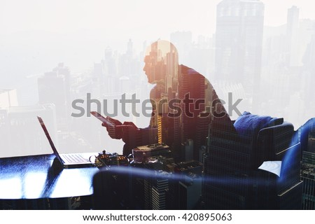 Double exposure silhouette of successful businessman is working in office company with net-book and touch pad. Thoughtful entrepreneur is using digital tablet and laptop computer for finance analyze
