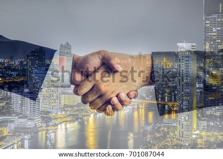 Double exposure the city, Businessmen is handshake to contact about them business, Business background. #701087044