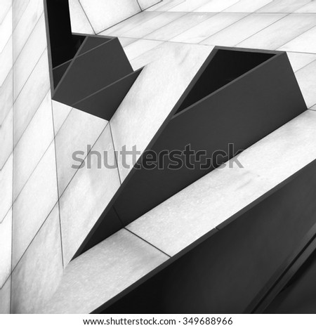 Double exposure tilt photo of walls consisting of rectangular white and black panels after digital alteration which transformed snapshots into notable architecture project resembling shelves on slopes