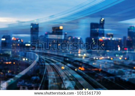 Double exposure train track with blurred light city office building, night view, abstract background