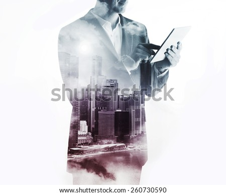 Double exposure with businessman using digital tablet