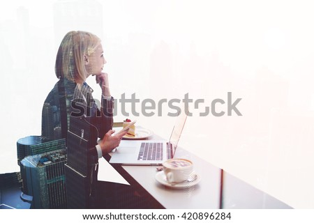 Double exposure with hipster girl with mobile phone thoughtful look away, while is sitting  at the table of modern coffee shop with open laptop computer. Woman freelancer using cell phone and net-book