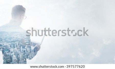 Double exposure young bearded businessman wearing black shirt holding contemporary notebook hands.Isolated white,modern city background.Blank screen ready for your business message.Wide mockup