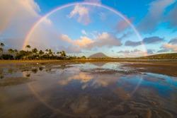 double full circle rainbow across tropical Hawaiian island bay with full circle reflections in the ocean water