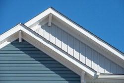 Double gable, with white decorative corbel, bracket, brace on a triangle gable roof, white soffit and fascia,  gray vertical and blue horizontal vinyl lap siding with blue sky background