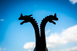 Double headed dragon or some other monstrous creature against blurred sky background.