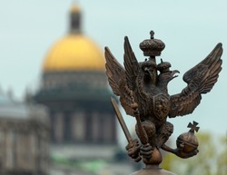 Double-headed eagle from Palace Square in St. Petersburg. Eagle statuette with symbols of power in its claws on the background of St. Isaac's Cathedral, Russia,