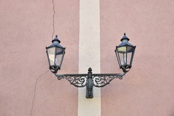 double lantern, ironwork, at pink painted house facade with white stripe and big crack