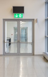 Double-leaf glass door with a green emergency exit lamp above it