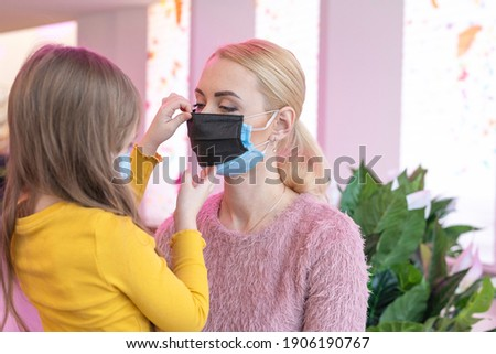double mask on the face. A woman wearing two medical masks at the same time, blue and blue Foto stock ©