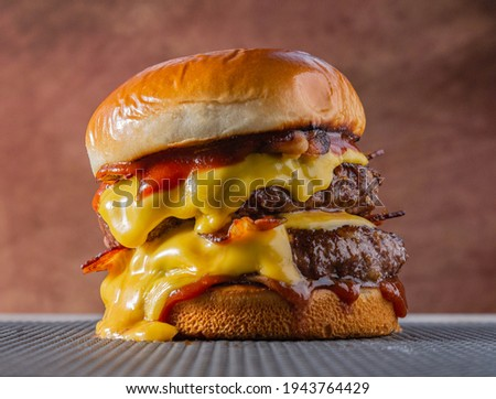 double meet Burger with melting cheddar cheese and bacon centralized on a gray surface and brown background.