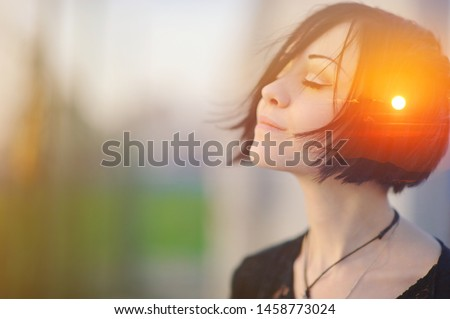 Double multiply exposure portrait of a dreamy cute woman meditating outdoors with eyes closed, combined with photograph of nature, sunrise or sunset, closeup. Psychology freedom power of mind concept