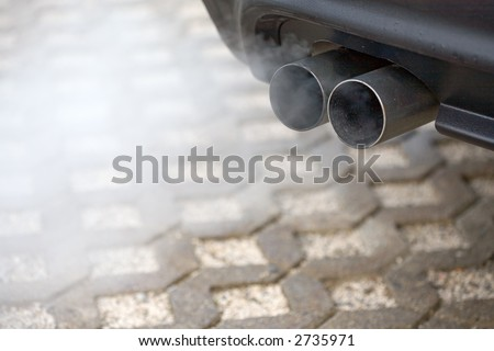 Double-Pipe-Exhaust of a car. Much Dust...
