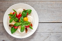 Double plated fresh farm style caprese salad on a weathered wooden board
