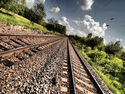 Double railroad track with HDR effect leading into the distance