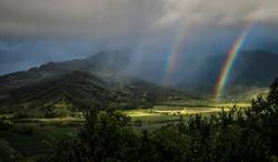 Double rainbow and sunbeams illuminate the taro fields at Kauai's Hanalai overlook.