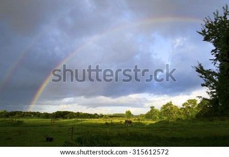 Double rainbow in the cloudy sky after a thunderstorm over a wide green country landscape with horse pasture, fields and trees, an idyllic rural background with copy space