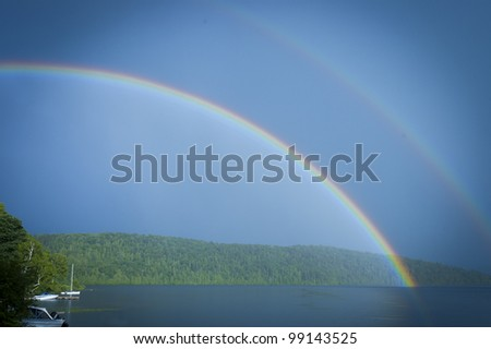 double rainbow over a lake with a beautiful blue sky in Quebec country, Canada