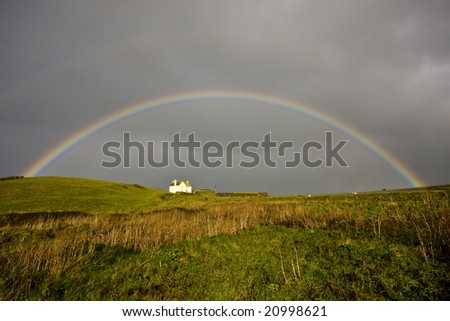 double rainbow over house with stormy sky