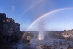 Double rainbow over Nakalele blowhole. Sunrays reflect on a spray coming from a blowhole creating beautiful color stripes