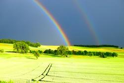 double rainbows on green fields in evening light