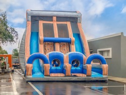 Double rock climb bounce house with slides on both sides at the downtown street fair.  Two stories high filled with contionus air flowing fans for maximum fun on a wet street.