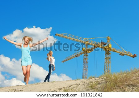 Double shape of beautiful girl against yellow cranes