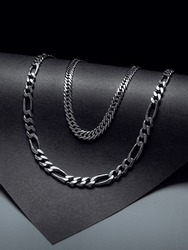 double silver chain necklace on black background with dark and rounded shapes close up