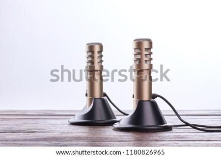 Double stereo microphone on wooden table. Stereo recorder microphone over white background. Professional stereo technology.