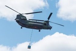 Double tri-rotor, heavy airlift, military helicopter, in service flight, carrying a small cargo load to a landing site.