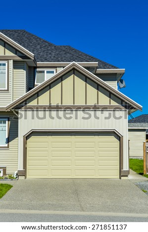 Double wide garage door of suburban house with concrete driveway in front.