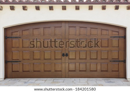 Double wooden swinging doors to a family home garage. The home is peach stucco. Also seen is the stone driveway and roof detail with shingles and wood beams.