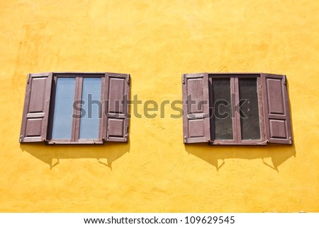 double wooden windows open on yellow wall.