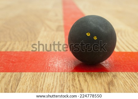 Double yellow dot black squash ball on the red t-line in squash court ストックフォト ©