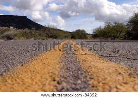 Double yellow line of a two lane road constricts into the vanishing point  in Arizona