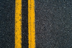 Double yellow line on black asphalt road.