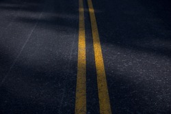 Double Yellow Line On Old Asphalt Road with sun light texture and background