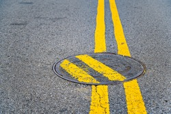 Double yellow lines painted over a manhole cover to humorous effect.