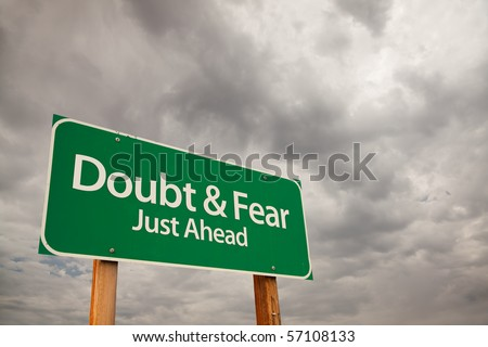 Doubt and Fear Just Ahead Green Road Sign with Dramatic Storm Clouds and Sky.