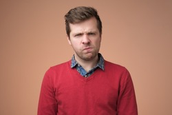 Doubt, mistrust, distrust concept. Doubtful mature caucasian man in red sweater looking with disbelief expression .